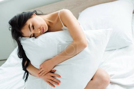 Photo for Attractive asian woman with closed eyes holding pillow while sitting on bed - Royalty Free Image