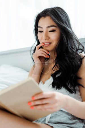 Photo for Selective focus of attractive thai woman reading book and touching face - Royalty Free Image
