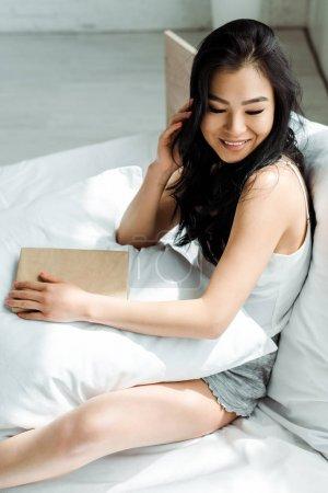 Photo pour Heureux asiatique fille toucher cheveux et tenant livre tandis que assis sur lit - image libre de droit