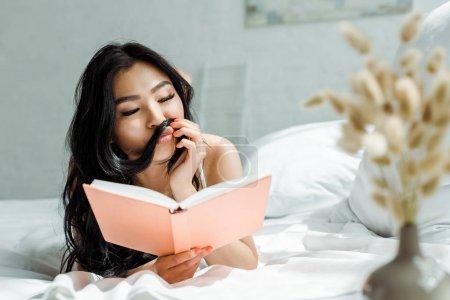 Photo pour Foyer sélectif de la fille asiatique avec le visage de canard touchant le cheveu tout en lisant le livre - image libre de droit