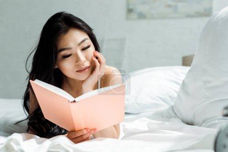 Photo pour Livre de lecture de femme thaï eillin attirante et se trouvant sur le lit à la maison - image libre de droit