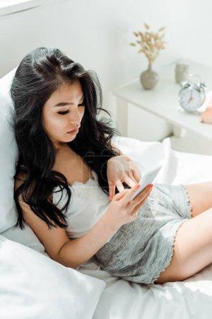 Photo pour Vue aérienne de la femme de thai de brunette utilisant le smartphone à la maison - image libre de droit
