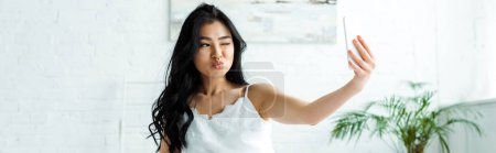 Photo pour Panoramic shot of asian girl with duck face taking selfie on smartphone - image libre de droit