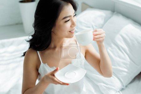 Photo pour Tasse heureuse de fixation de femme de brunette avec la boisson dans la chambre à coucher - image libre de droit