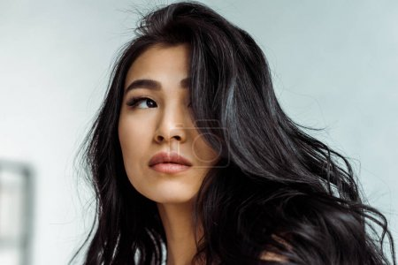 Photo pour Femme asiatique attirante et rêveuse pensant à la maison - image libre de droit