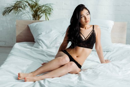 Photo pour Sexy thai woman in lace black lingerie lying on bed - image libre de droit