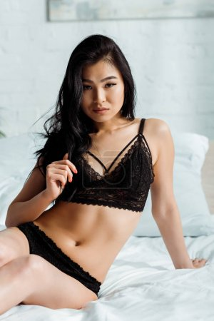 Photo for Sexy thai woman in lace black lingerie sitting on bed and looking at camera - Royalty Free Image