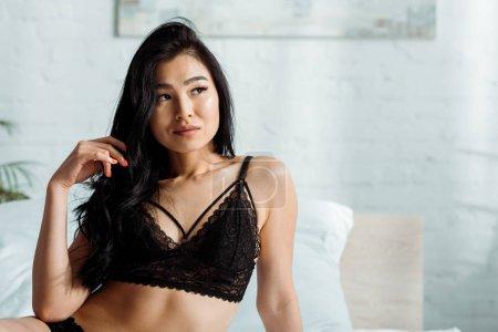 Photo pour Femme brune thaï pensive dans la lingerie noire à la maison - image libre de droit