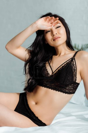 Photo pour Brunette thai woman sitting in black underwear on bed - image libre de droit