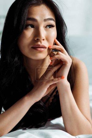 Photo pour Femme de thai de brunette dans le visage touchant noir de sous-vêtements - image libre de droit