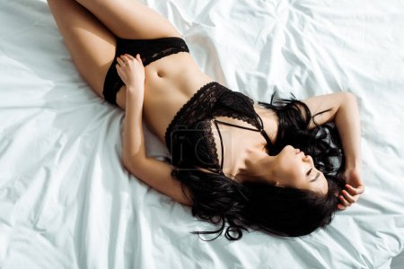 top view of sensual thai woman in black underwear lying on bed