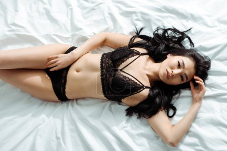 Photo pour Top view of pretty  thai woman in black sexy underwear lying on bed - image libre de droit