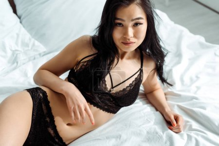 Photo pour Overhead view of thai woman in black sexy underwear lying on bed - image libre de droit