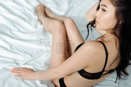Photo pour Overhead view of pretty thai woman in black sexy underwear sitting on bed - image libre de droit