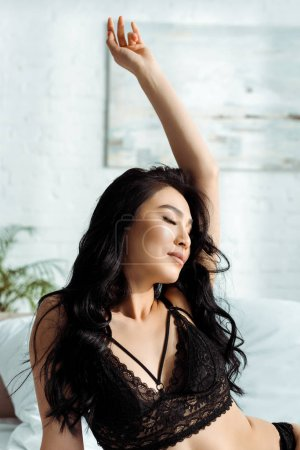 sensual thai woman with closed eyes in sexy lace bra with hand above head