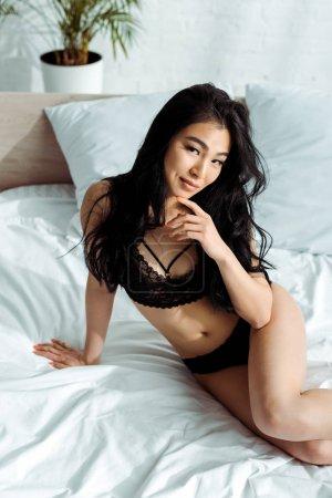 Photo pour Vue au-dessus de la jolie femme thaïe dans les sous-vêtements sexy noirs s'asseyant sur le lit et regardant l'appareil-photo - image libre de droit