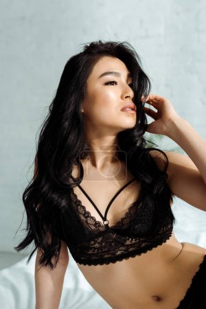 Photo pour Seductive asian young woman in lace underwear touching hair - image libre de droit