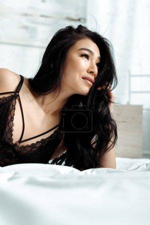 Photo pour Foyer sélectif de jolie femme thai en noir sexy sous-vêtements couché sur le lit - image libre de droit