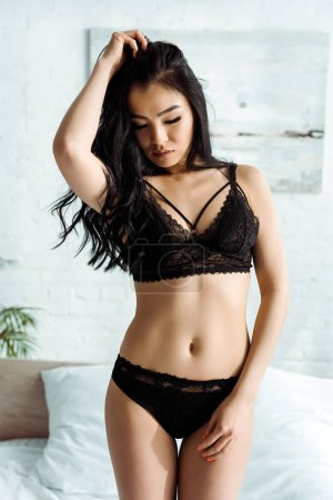Photo for Seductive asian young woman in lace underwear standing and touching hair - Royalty Free Image