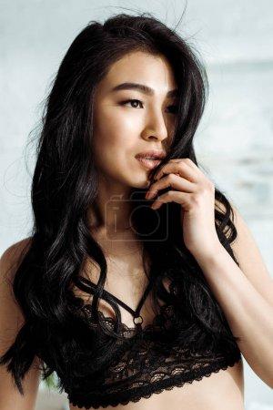 Photo pour Femme thaïe attirante dans le soutien-gorge noir de dentelle touchant le visage - image libre de droit