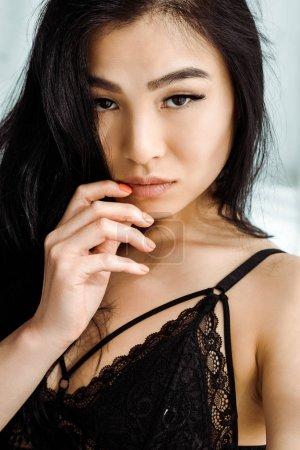 Photo pour Sexy asiatique femme en dentelle sous-vêtements debout et touchant visage - image libre de droit
