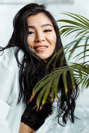 selective focus of happy asian woman looking at camera near plant