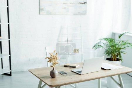 Photo pour Ordinateur portable et smartphone avec écran blanc sur une table en bois dans un bureau moderne - image libre de droit