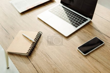 Photo for Smartphone with blank screen near laptop and notebook with pen - Royalty Free Image