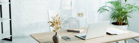 Photo pour Plan panoramique d'ordinateur portable et smartphone sur une table en bois dans un bureau moderne - image libre de droit