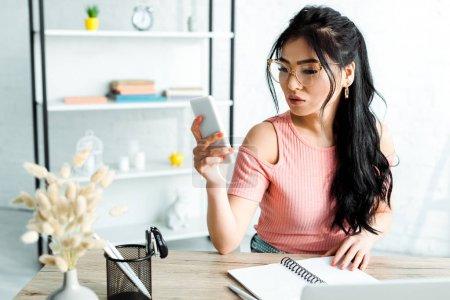 Photo pour Focus sélectif de femme d'affaires asiatique attrayante dans les lunettes à l'aide d'un smartphone dans le bureau - image libre de droit