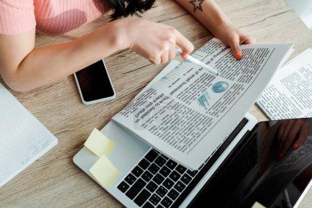 Photo pour Vue recadrée d'une jeune femme tenant un journal près d'appareils numériques - image libre de droit