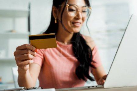 Foto de Enfoque selectivo de la mujer asiática en gafas que sostienen tarjeta de crédito y el uso de la computadora portátil - Imagen libre de derechos