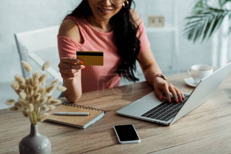 vue recadrée de femme asiatique tenant carte de crédit près d'un ordinateur portable et smartphone