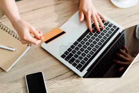 Photo pour Vue recadrée de jeune femme retenant la carte de crédit tout en utilisant l'ordinateur portatif - image libre de droit