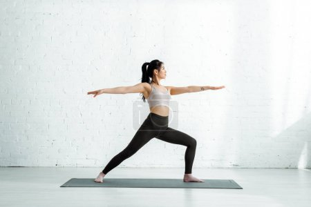 Photo pour Attractive thai woman standing with outstretched hands on yoga mat - image libre de droit