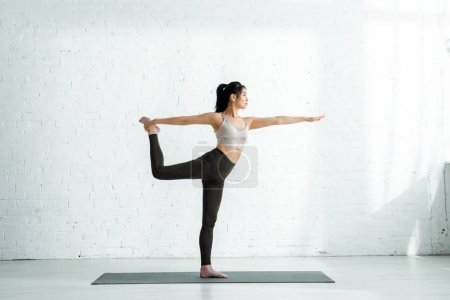 Photo for Calm thai woman doing exercise while standing on yoga mat - Royalty Free Image