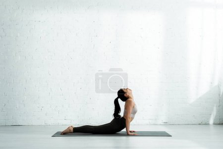 jolie femme thai faire de l'exercice sur tapis de yoga
