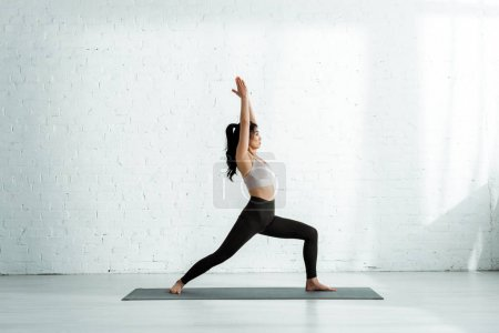 Photo for Beautiful brunette thai woman doing exercise on yoga mat - Royalty Free Image