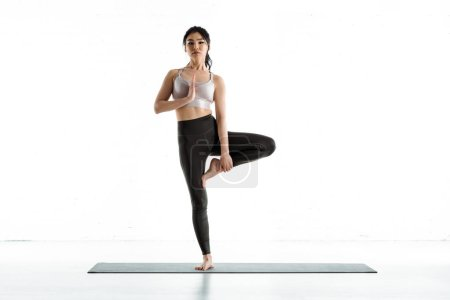 Photo pour Brunette thai woman standing on yoga mat and doing exercise on white - image libre de droit