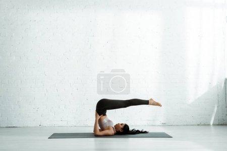 Photo pour Belle femme asiatique faisant l'exercice sur le tapis de yoga près du mur de briques - image libre de droit