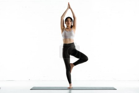 Photo pour Attractive thai woman standing on yoga mat and doing exercise on white - image libre de droit