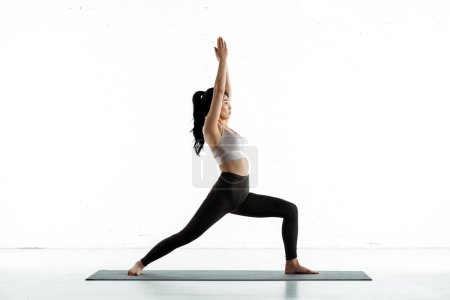 Photo pour Thai woman standing on yoga mat and doing exercise on white - image libre de droit