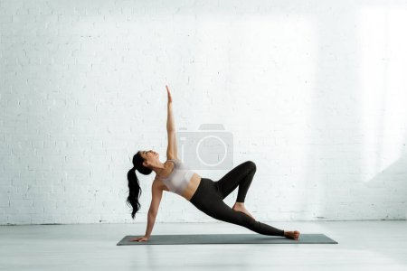 Photo pour Peaceful thai woman doing exercise on yoga mat near brick wall - image libre de droit