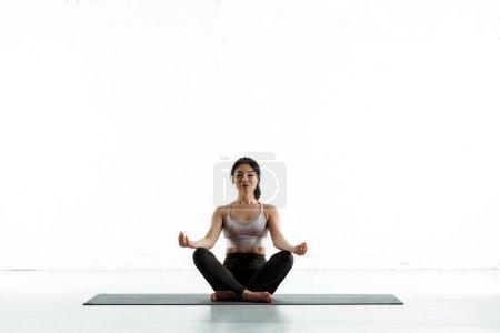 Photo pour Calm asian woman sitting on yoga mat and doing exercise on white - image libre de droit