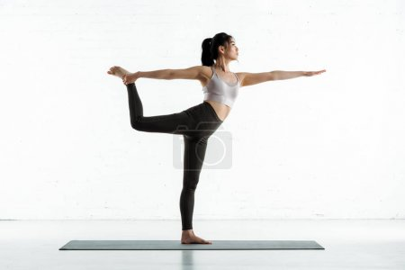 Photo pour Calm thai woman standing on yoga mat and doing exercise on white - image libre de droit