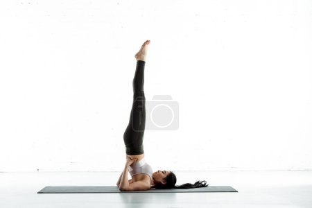 Photo pour Brunette thai woman on yoga mat doing exercise on white - image libre de droit