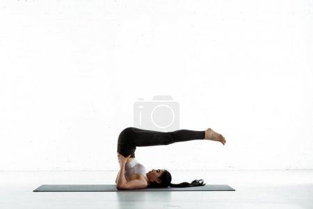Photo pour Brunette asiatique femme avec pieds nus faire exercice sur blanc - image libre de droit