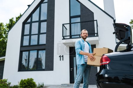 Photo for Low angle view of cheerful man holding boxes near car and modern house - Royalty Free Image