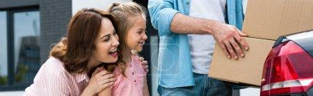 Photo pour Plan panoramique d'enfant heureux et mère souriant près de l'homme avec des boîtes - image libre de droit