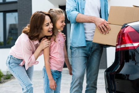 Photo for Cropped view of man holding boxes near happy kid and wife - Royalty Free Image